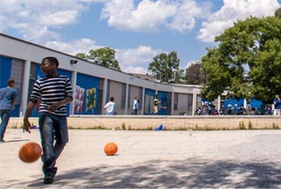 photo: child playing basketball in paved schoolyard