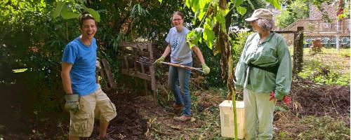Three people laughing near compost bin