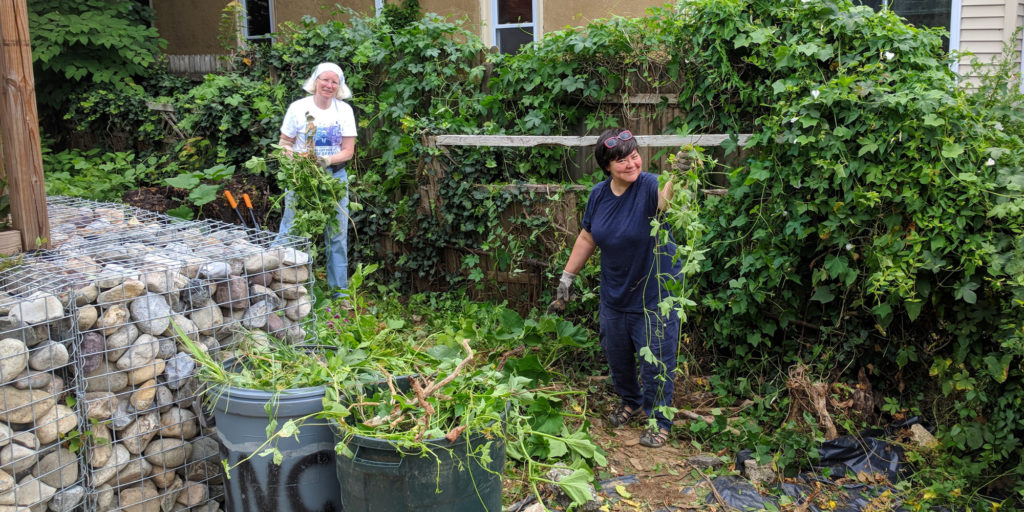 photo: two women pulling weeds by a fence
