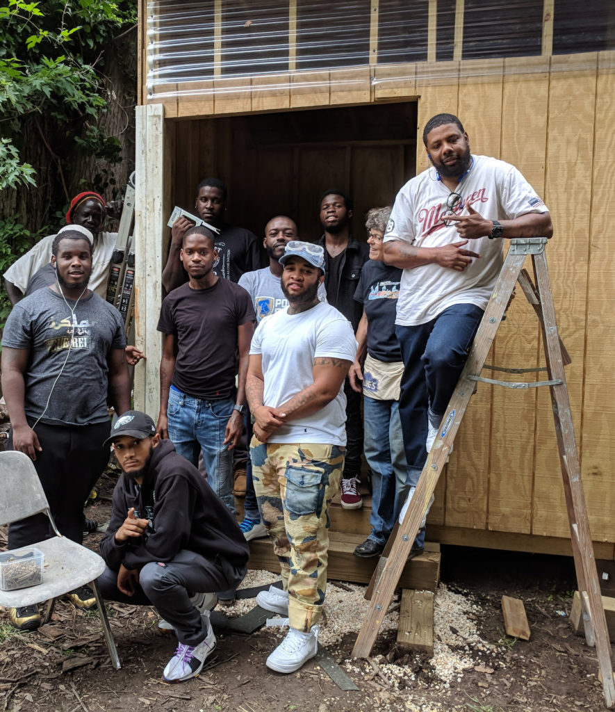 photo: group of carpenters gathered at door of shed