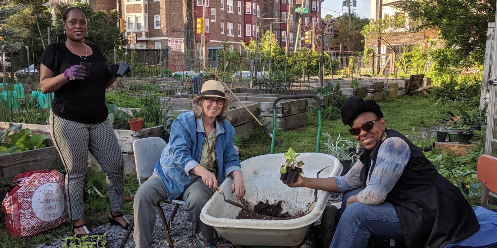 3 women potting plants at a wheelbarrow